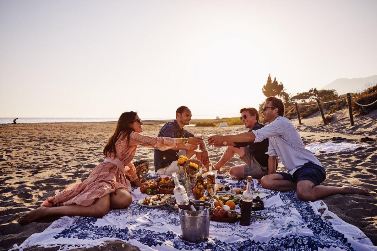 groep mensen picknick op strand teaser