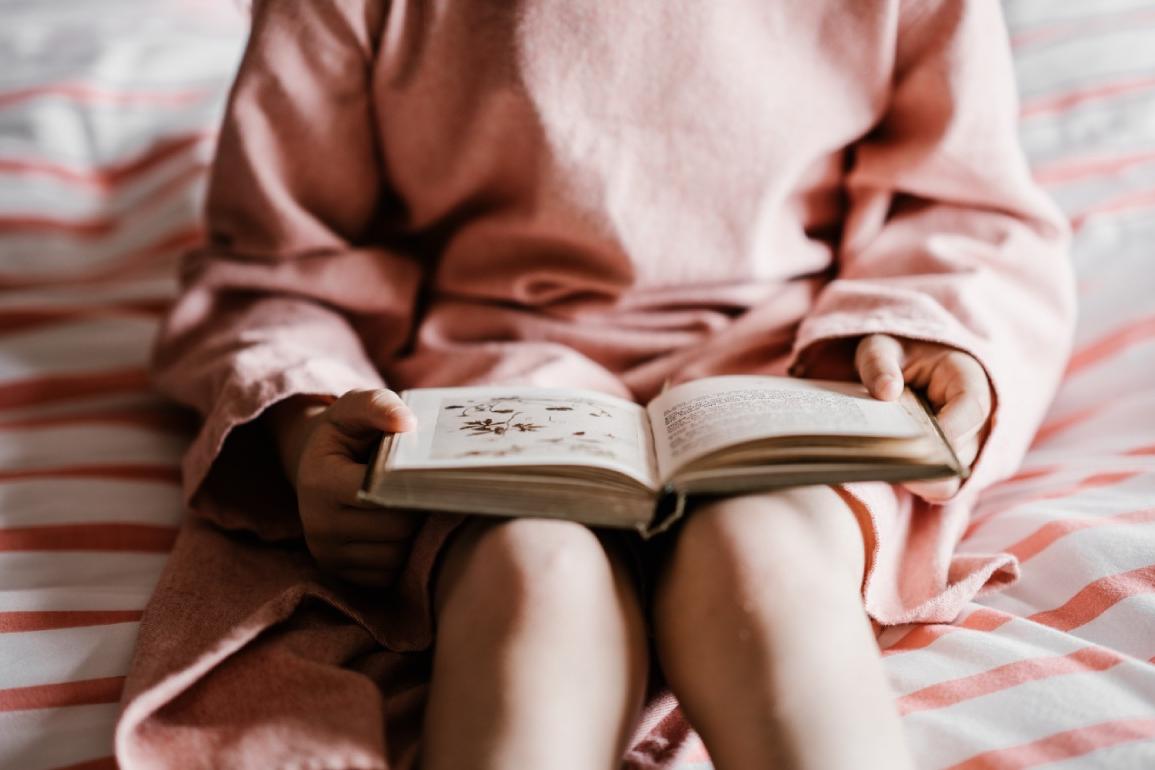iemand zit op bed met boek op schoot