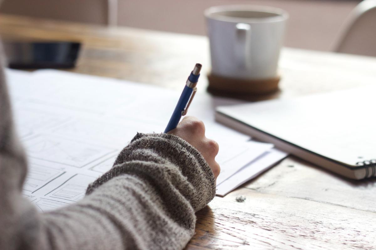 persoon houdt balpen vast en schrijft op een blad