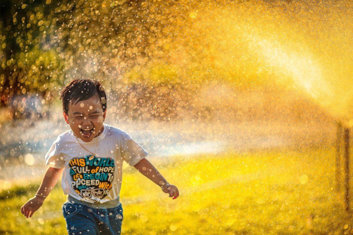 kind lacht onder sproeier