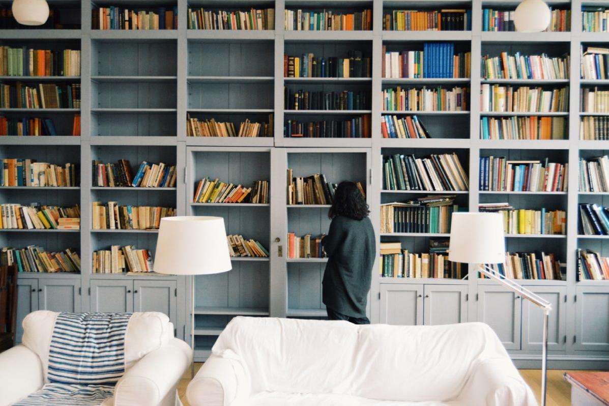 persoon staat voor boekenkast