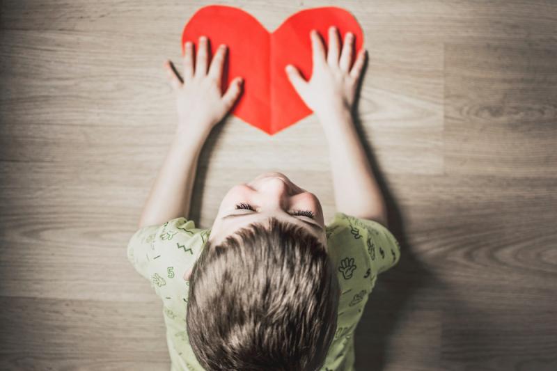 kind met handen op papieren rood hartje op tafel