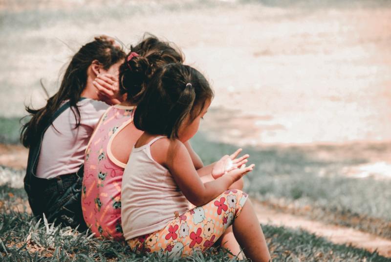3 kinderen zitten op het gras