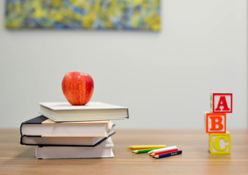stapel boeken met appel op en schoolmateriaal