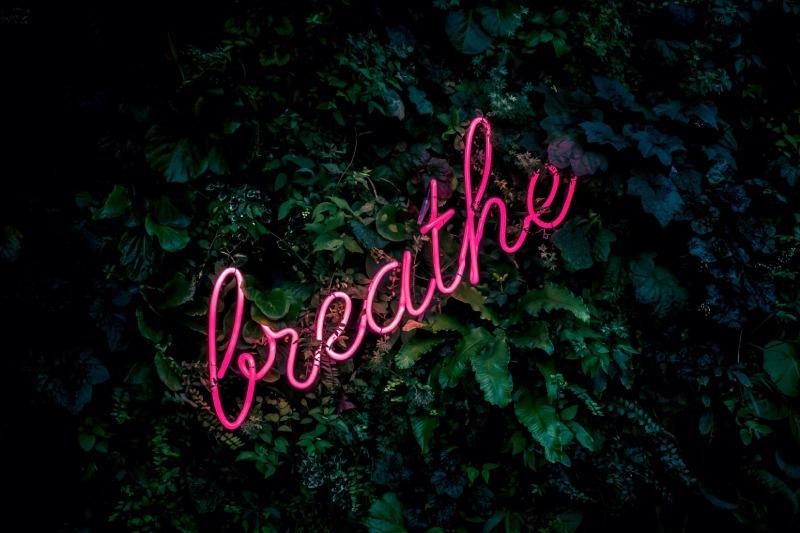 foto neonlicht 'breathe' met groene bladeren op de achtergrond
