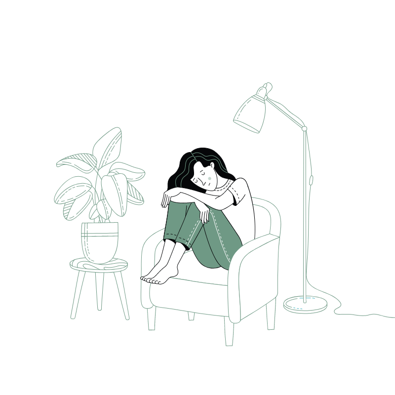 meisje zit met hoofd naar omlaag in kleermakerszit in fauteuil naast plant en staanlamp