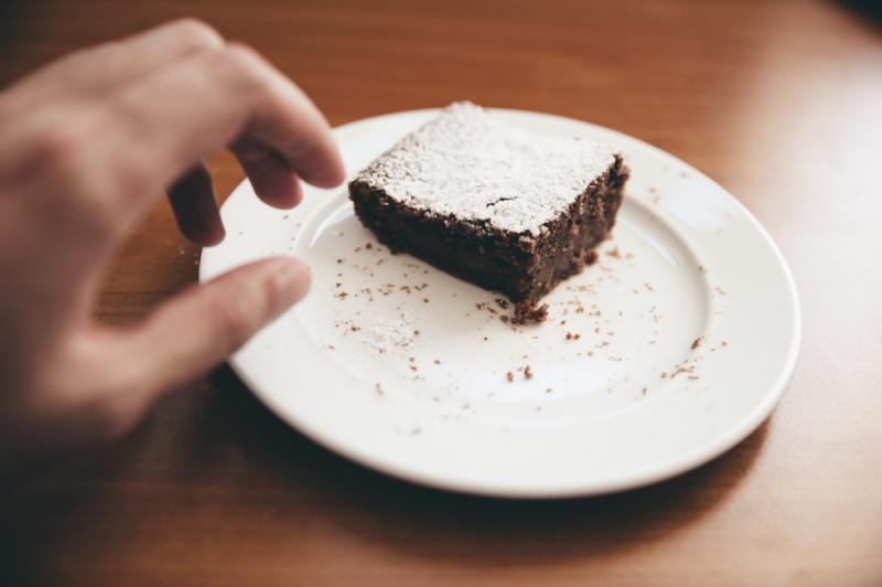 hand die naar brownie grijpt