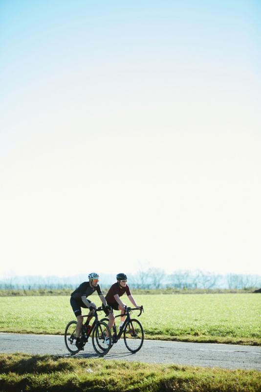 2 personen op de weg met de fiets met groen landschap op achtergrond