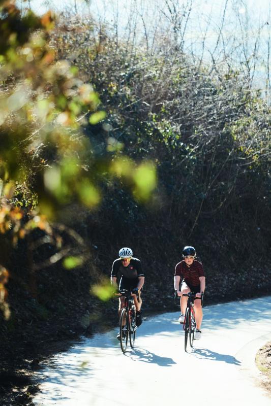 2 personen fietsen op de weg met bomen op achtergrond
