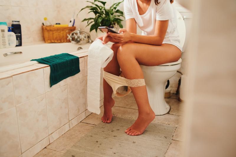 vrouw zit op toilet